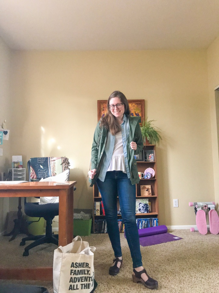 Shelby in a white peplum tee layered with a button down chambray unbuttoned with an olive utility jacket, dark wash skinny jeans in burgundy clogs