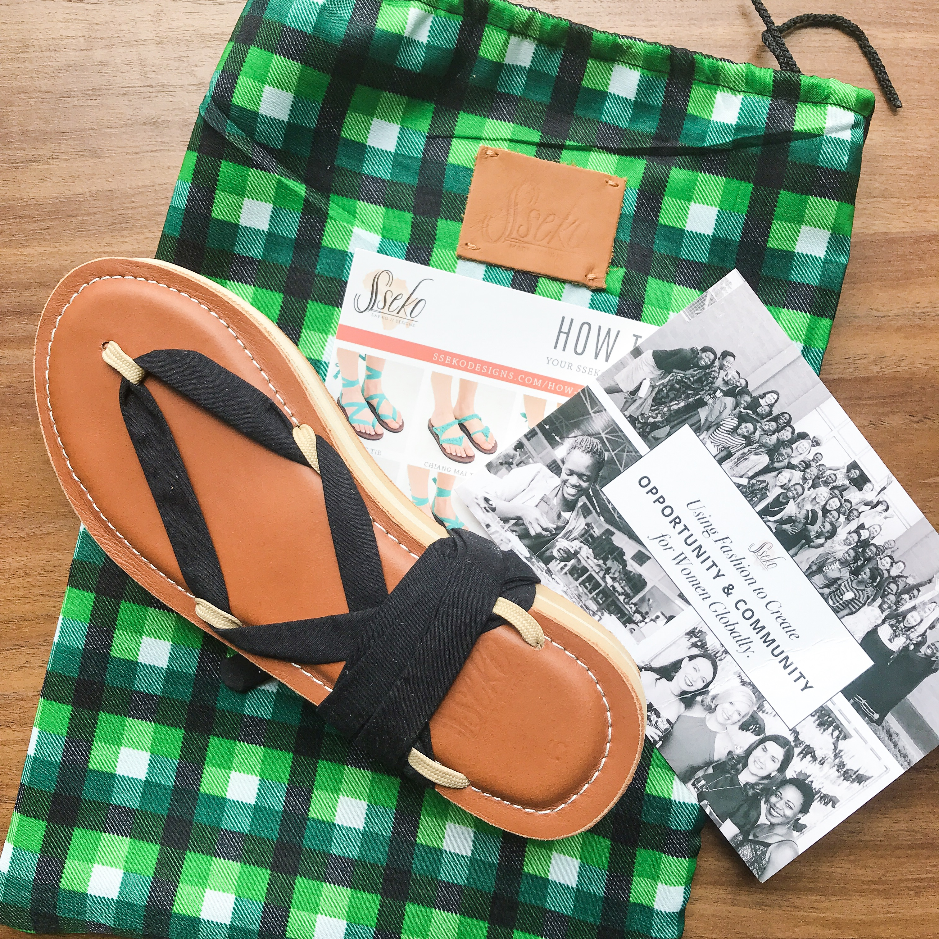 Ribbon Sandals wrapped together on top of a green drawstring bag