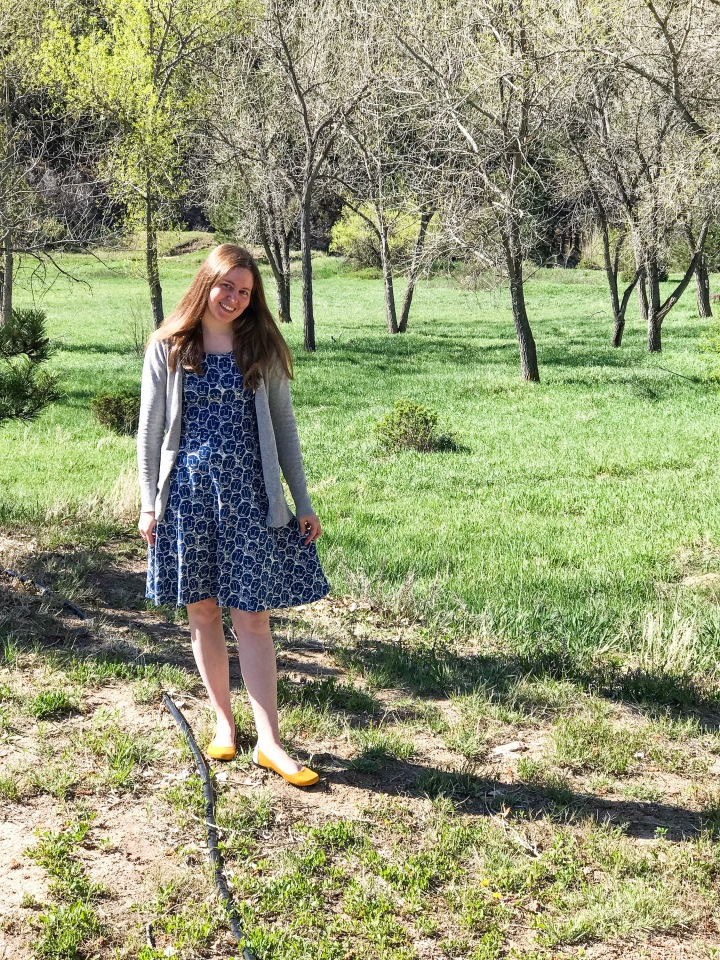 Shelby wearing Mata Traders Dress, under a gray cardigan, with mustard flats in front of green field.