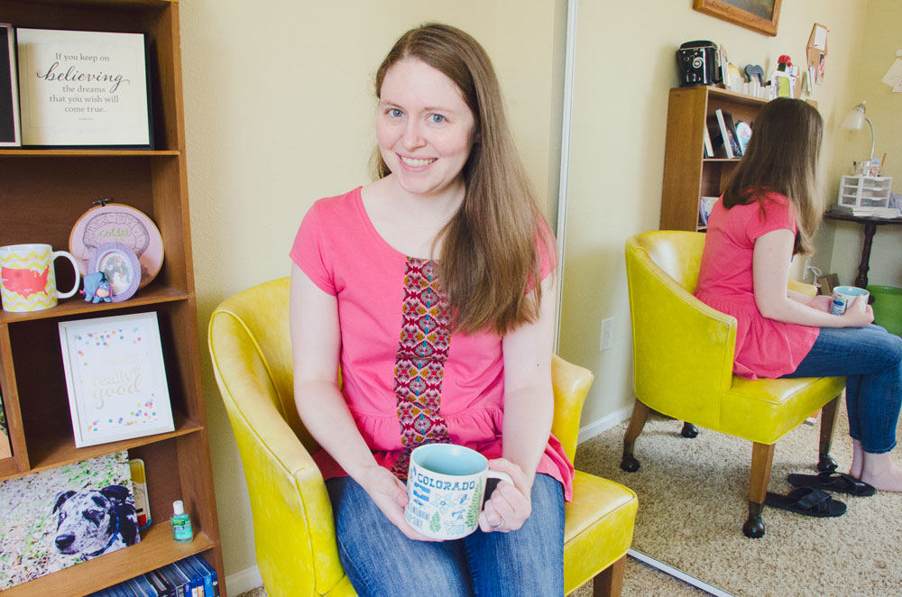 Shelby sitting in a yellow barrel back chair in a pink top holding a coffee cup.